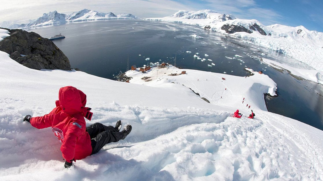 Small group of expedition cruisers wearing their red parkas and sliding down a steep path in the snow on Antarctica, with a research base and their small ship in the distance.