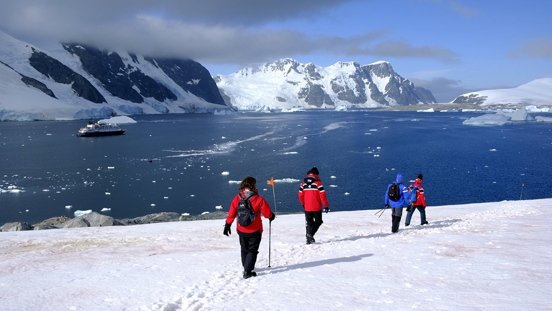 Antarctic travelers walk along a prescribed path in the snow with calm waters and their expedition ship in the background, on a sunny day during the Whale Science Voyage.
