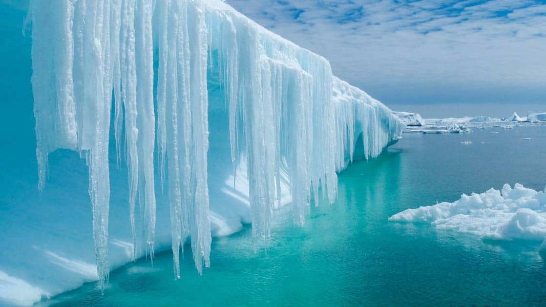 crystalline iceberg with icicles hanging into the water in antarctica