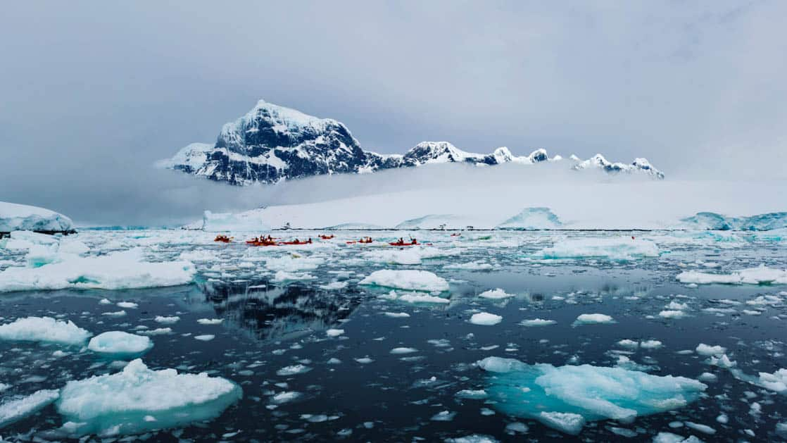 overlooking a calm antarctic ocean full of floating icebergs with a large mountain in the distance