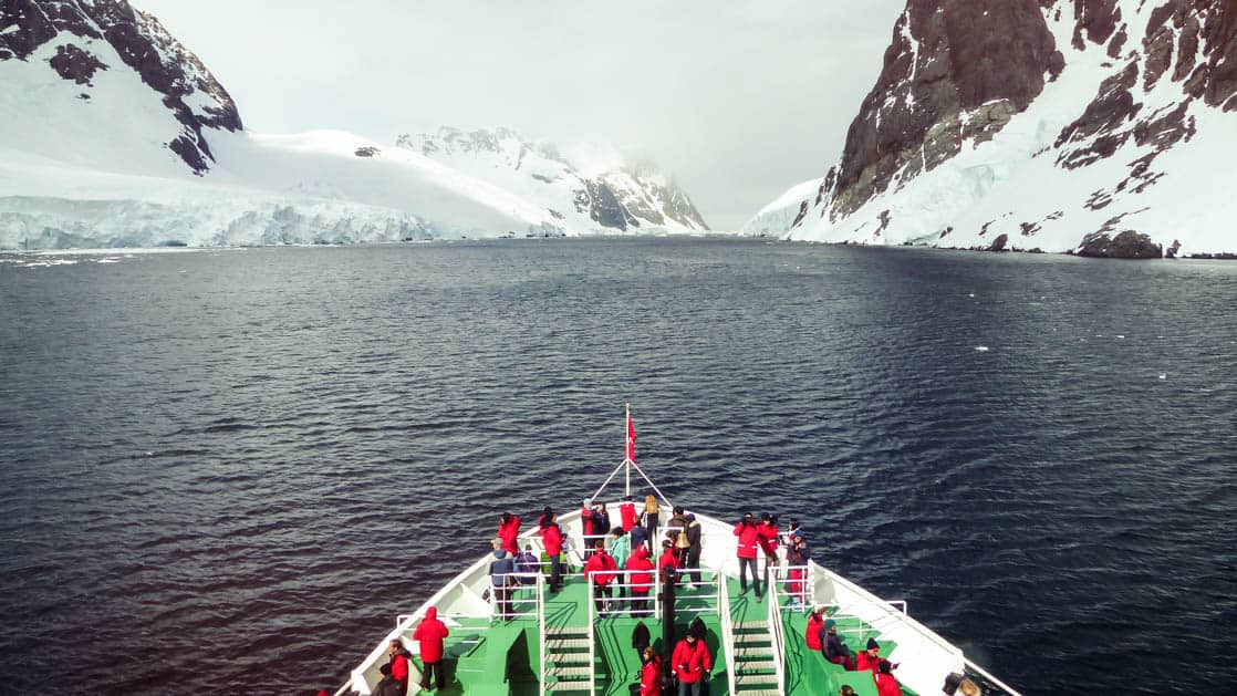 antarctica expedition ship passengers standing on the bow looking forward across the sea to snowy mountains ahead on an overcast day