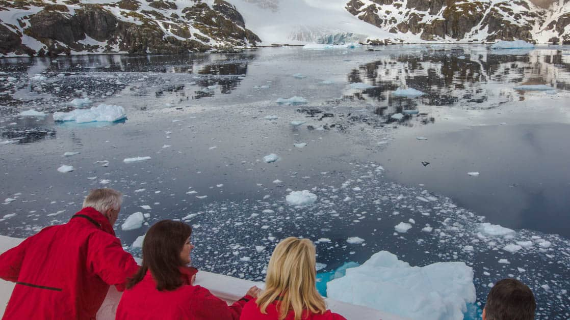 travelers look beyond the bow of an antarctica expedition ship at glassy water full of icebergs with mountains in the distance