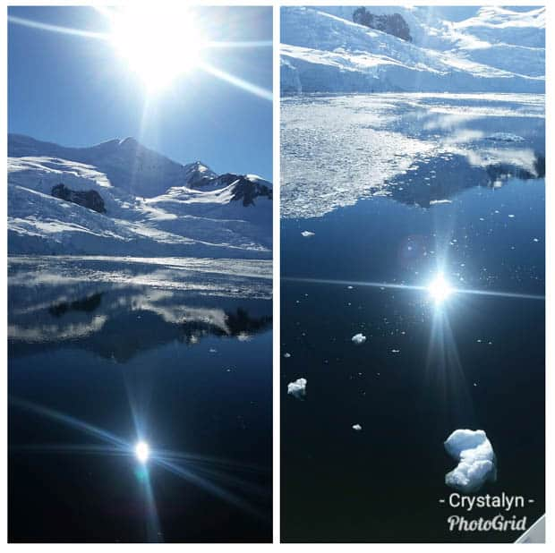 Sun with blue sky reflection in the calm icy waters of Antarctica seen from a small cruise ship.