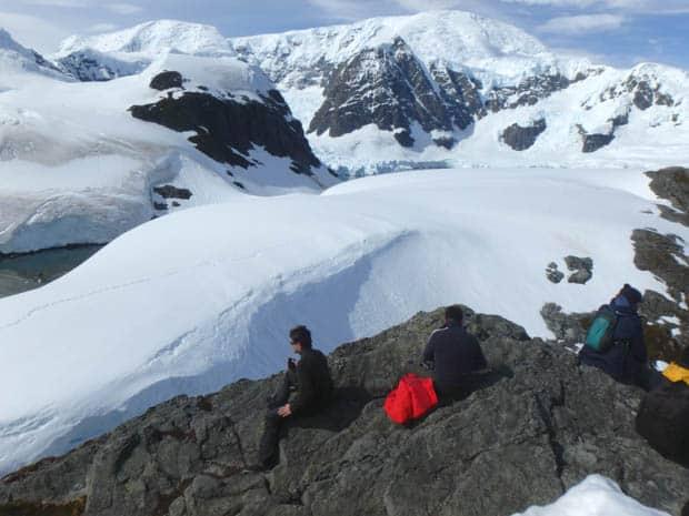 Small ship cruise guests on hiking tour in Antarctica stopping for a break.