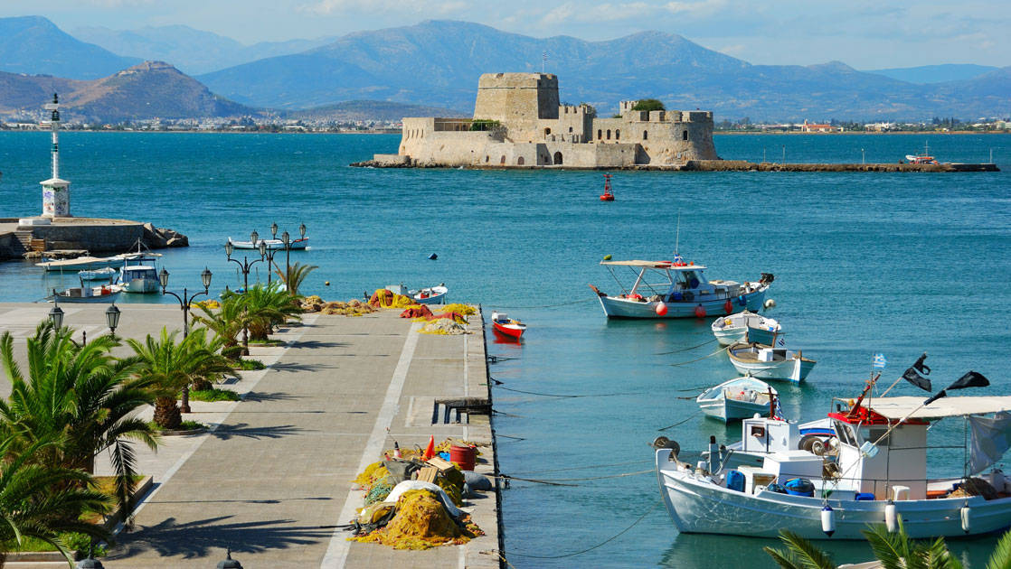 Turquoise sea with a beige castle in the background & paved promenade along the water in the foreground, in Nafplion, Greece.