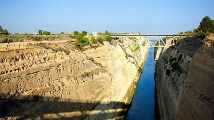 a canal runs between dirt slopes in corinth, leading to the aegean sea