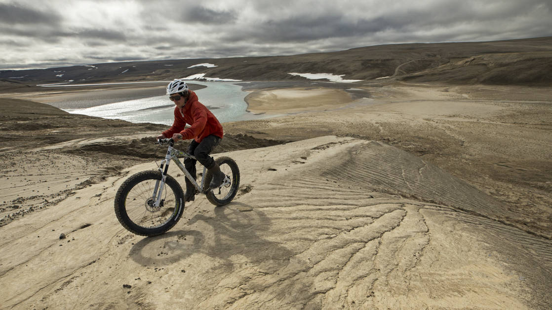 A mountain biker riding above a beach in the Arctic.
