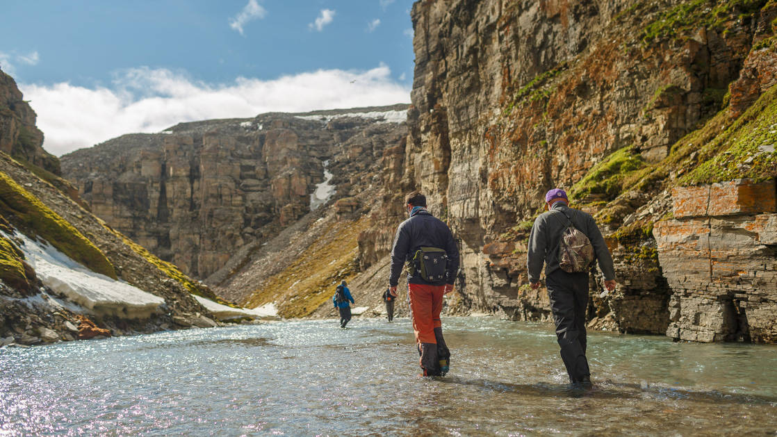 Two Arctic travelers hiking along a riverbank in a canyon.