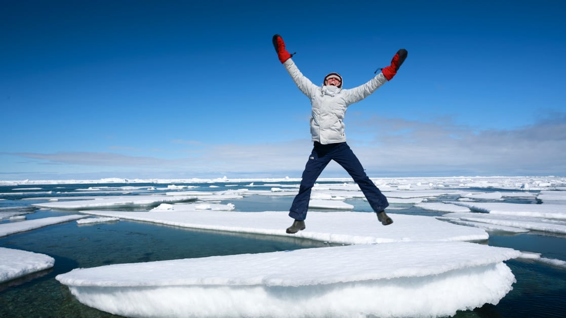 A woman jumping for joy on an ice berg in the Arctic.