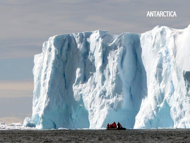 People on a raft in front of a large Antarctic iceberg