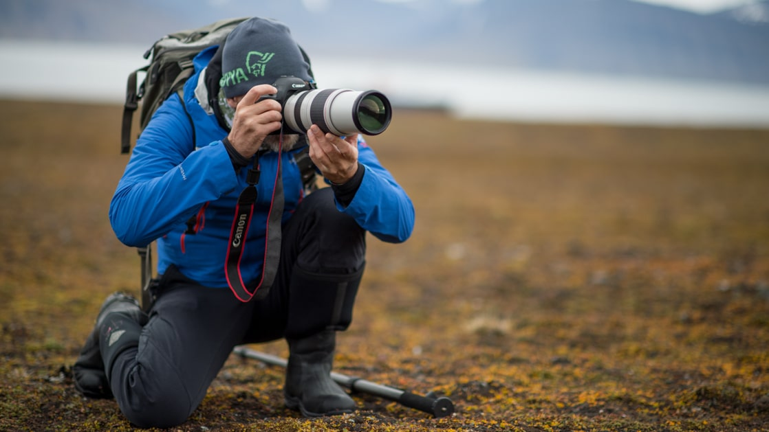 Male photographer in bright blue jacket kneels down by green and gold tundra to take a photo.