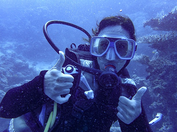 Woman SCUBA diving with two thumbs up in the Great Barrier Reef