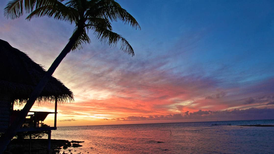 lone beachside hut overlooking calm ocean with a gorgeous vibrant sunset in the pacific islands