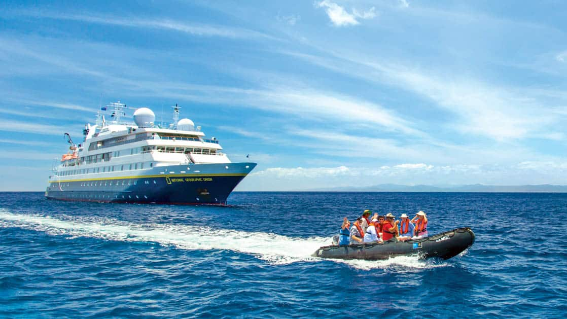 Guests on Zodiac in front of the National Geographic Orion small ship in Fiji, South Pacific on a sunny day