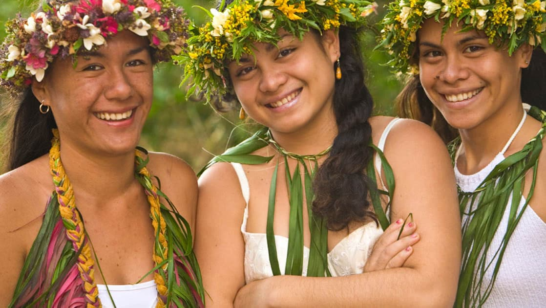 smiling indigenous pacific islands women wearing leaf and flower necklaces and head dresses