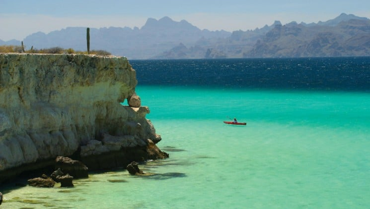 aerial of kayaker in turquoise waters beside large cliff in baja