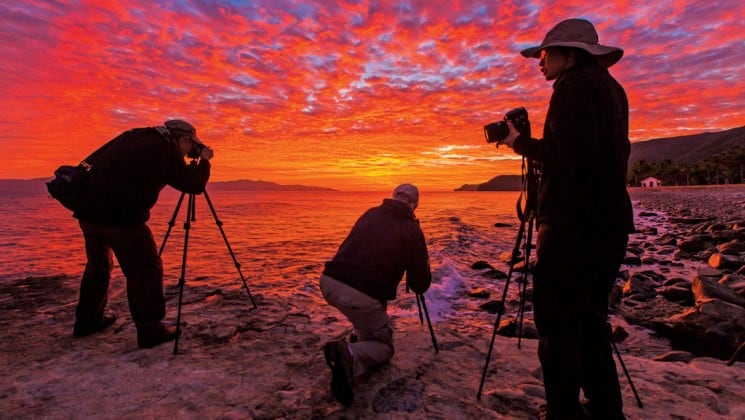 three photographers during red sunset in baja california
