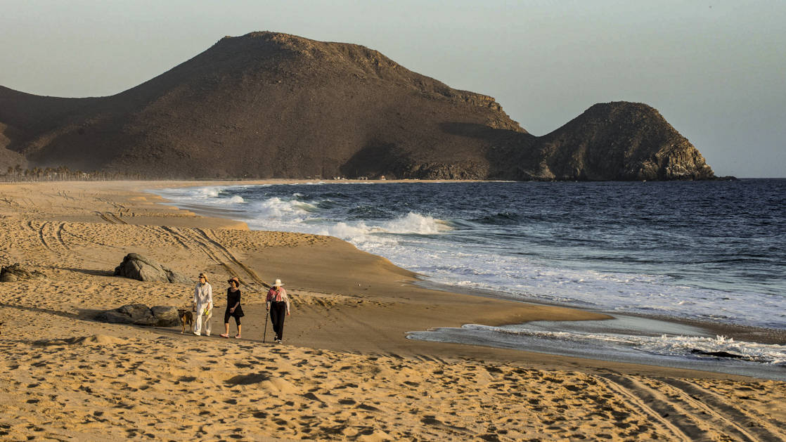 three people walking along the ocean on a sandy beach as the sun is starting to go down