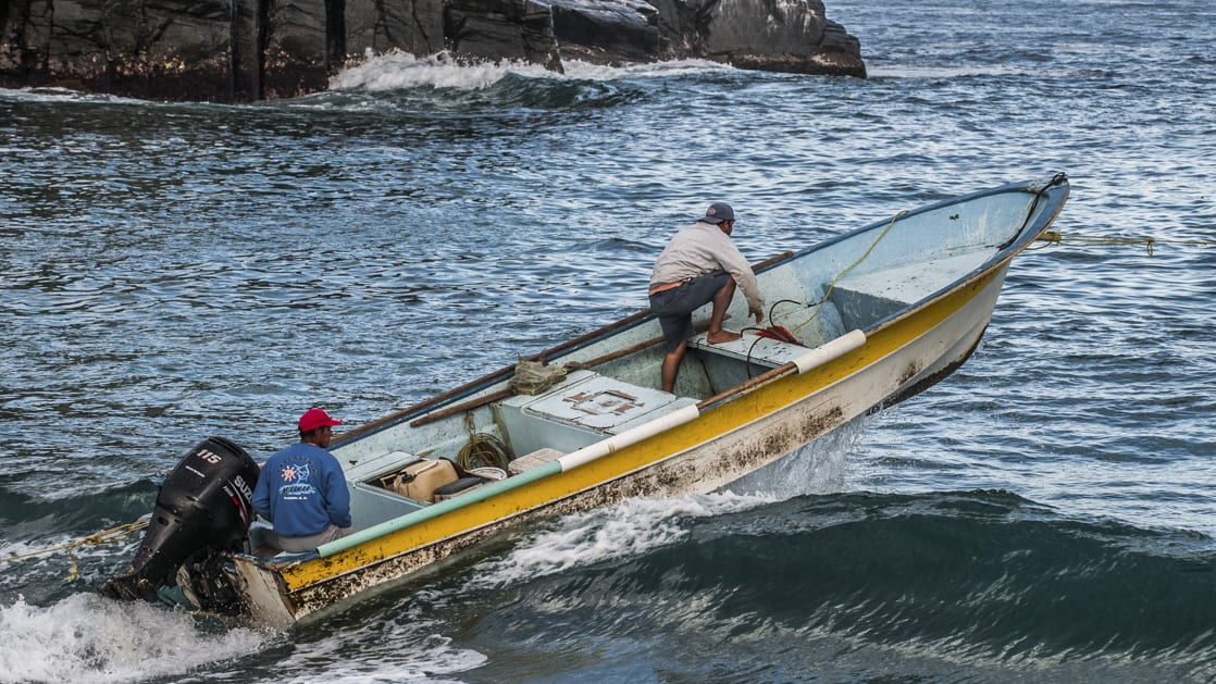two local men in a small boat going over a wave near the coastline in baja california