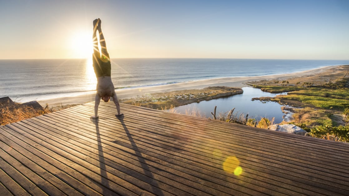 person doing a yoga hand stand on a platform above the beach during the sunset
