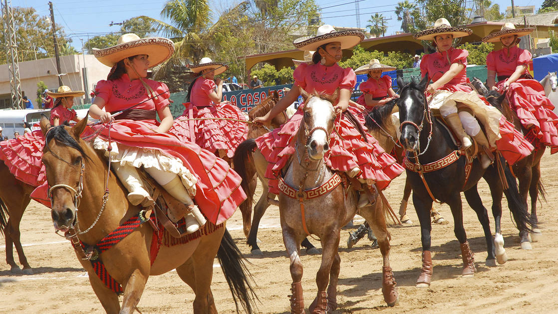 local women rancheras on horses in traditional costume performing in baja california
