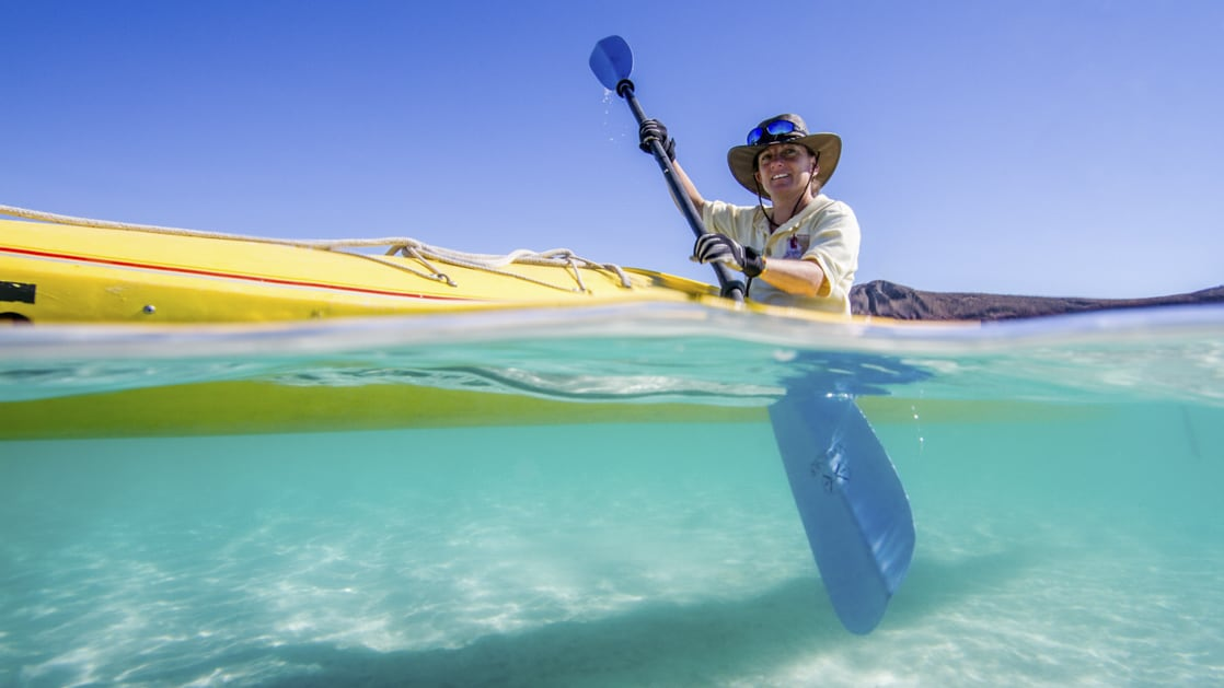 half underwater view of a kayaker paddling in the clear blue waters of baja california