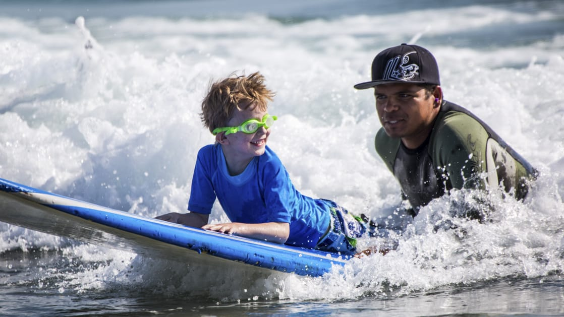 boy laying on a surfboard with his local guide during a lesson and trying to catch a wave