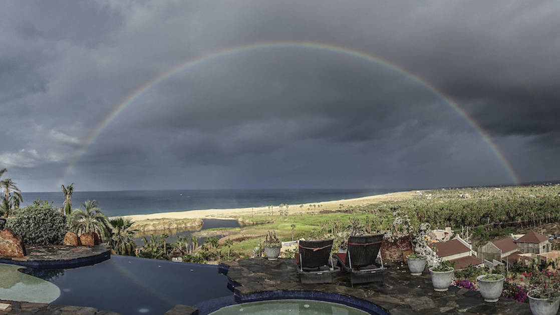 full rainbow over the ocean seen from the outdoor lounge area at the todos santos in pool