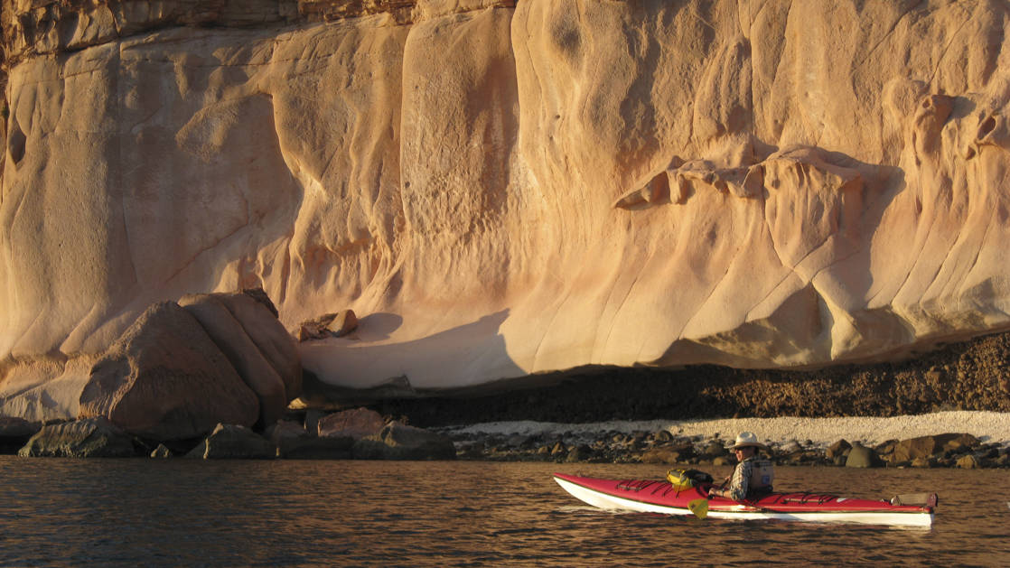 a kayaker paddling close the the uniquely shaped coastline cliffs of baja california