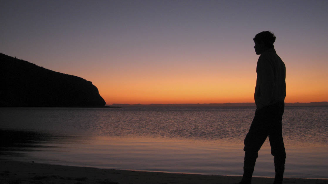 silhouette of a person walking on the beach during an orange sunset in baja california