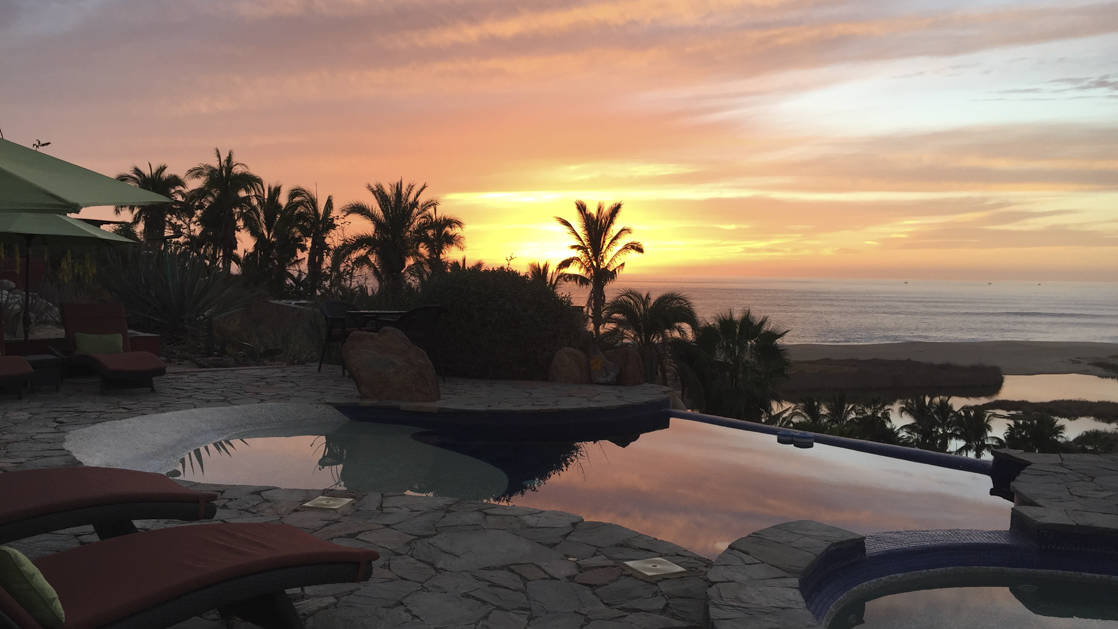 infinity pool and jacuzzi overlooking the beach in baja california at the todos santos inn with lounge chairs and palm trees around during the sunset