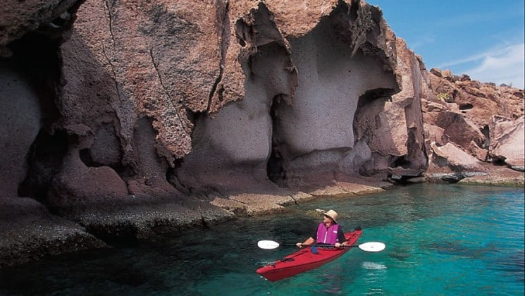 kayaker beside cliff on baja: a remarkable journey cruise