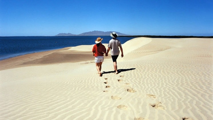 couple walking on beach during shore excursion on baja: a remarkable journey cruise