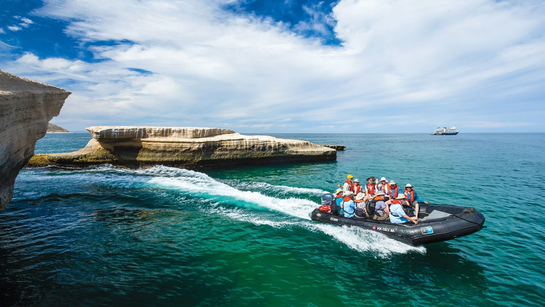 Zodiac with Baja travelers zooms through emerald waters on a sunny day during the Remarkable Journey cruise.