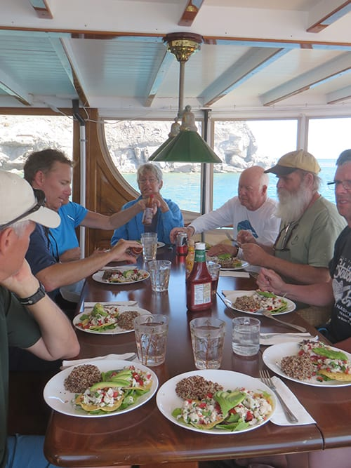 baja california small ship cruise passengers talk and eat at a table on a covered deck of the westward