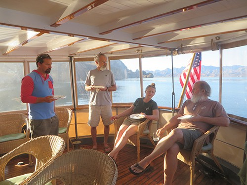baja small ship cruise passengers relax on a covered deck of the westward