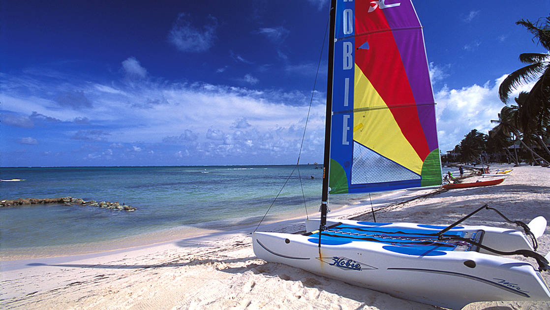 A hobie sailboat on the beach with bright sails
