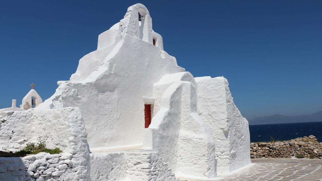 Stucco, bright white chapel with red door sits beside deep blue ocean, seen on the Best of Greece & Turkey small ship cruise.