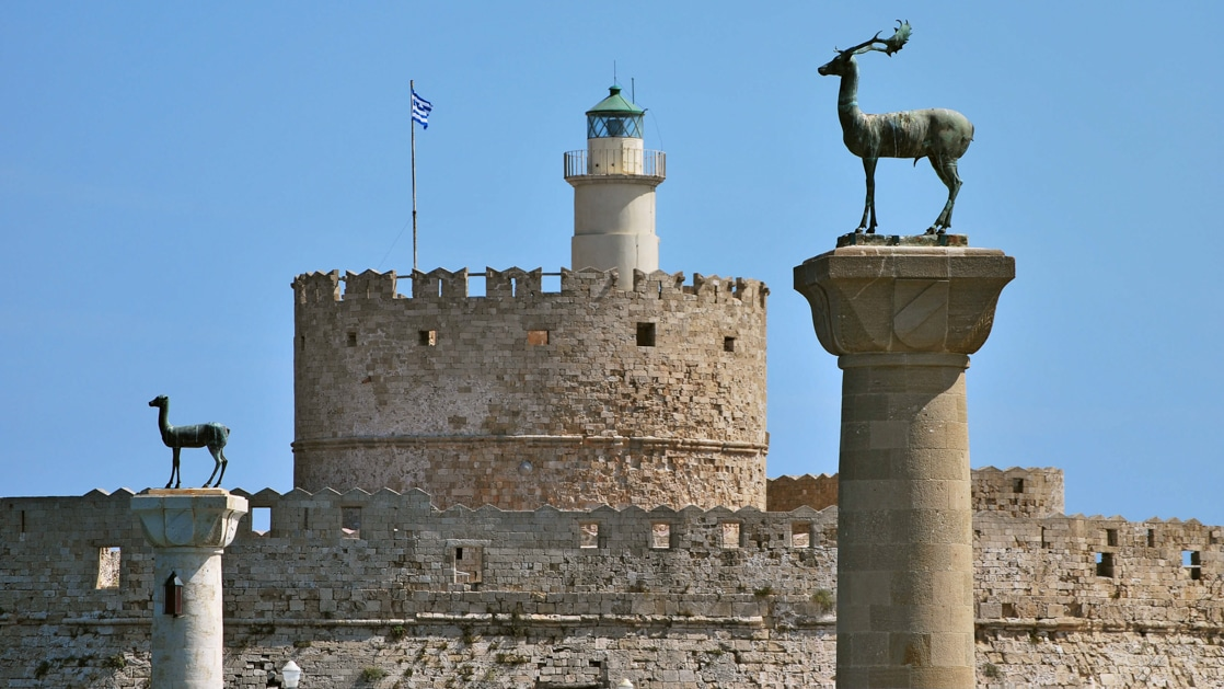 Beige castle with a Greek flag, lighthouse & pillars with deer statues, seen during the Best of Greece & Turkey voyage.