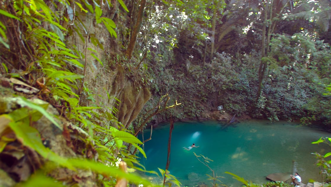 The Blue Hole in Belize with a swimmer in the turquoise water and green foliage surrounding it.