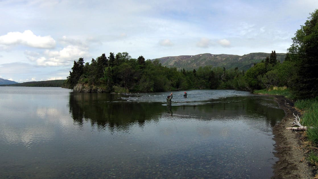 Several people wading in the water near the beach fishing in katmai alaska