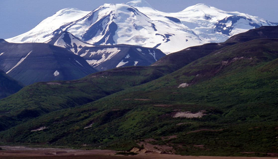 green hilly mountains in front of larger snow capped peaks in the katmai peninsula of alaska