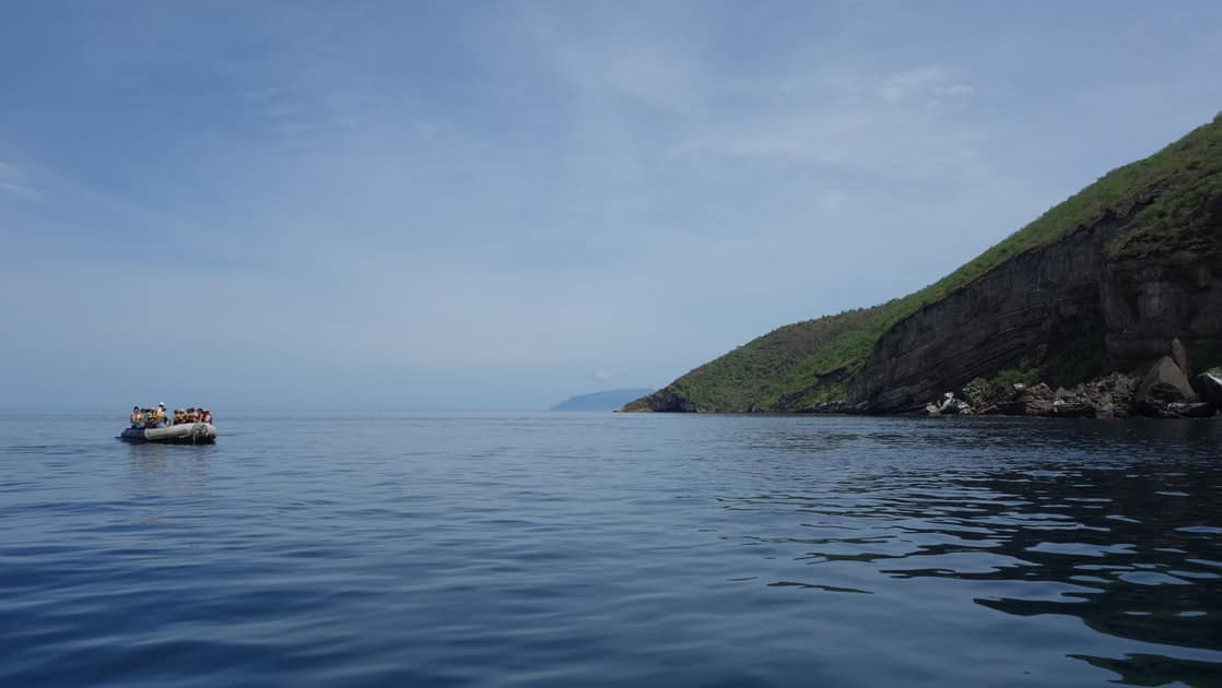 Zodiac cruise with travelers on calm waters offshore from a Galapagos Island