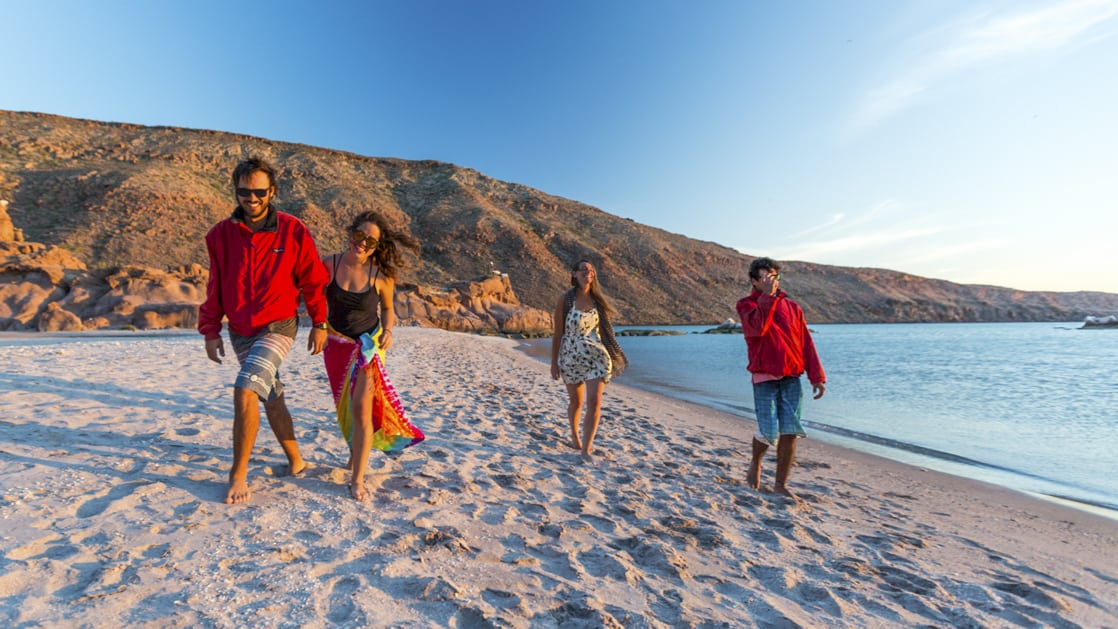 A group of Baja travelers walking along a remote beach.