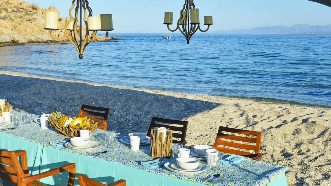 A dining table set nicely with candles, chandeliers on the beach.