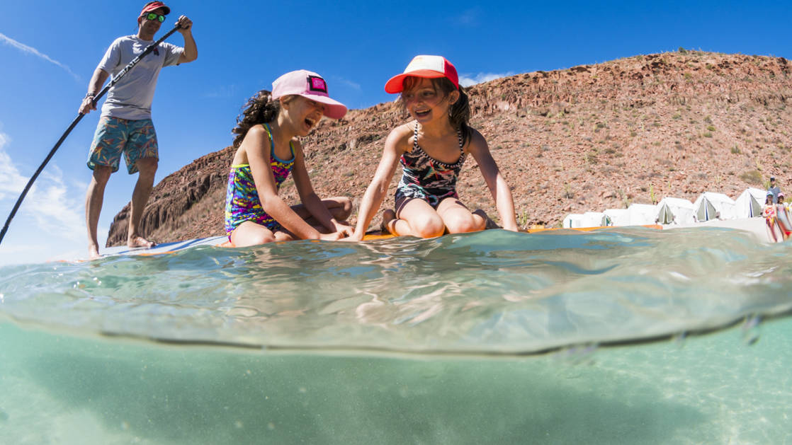 Two little girls laughing on a paddleboard with a man paddling.