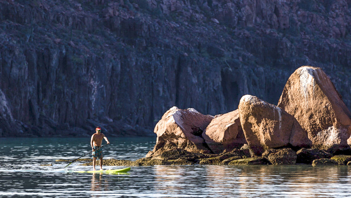 A man paddleboarding by a outcropping of rocks