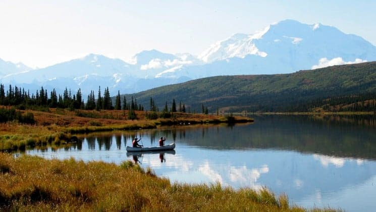 two people paddling canoe across lake on camp denali adventure