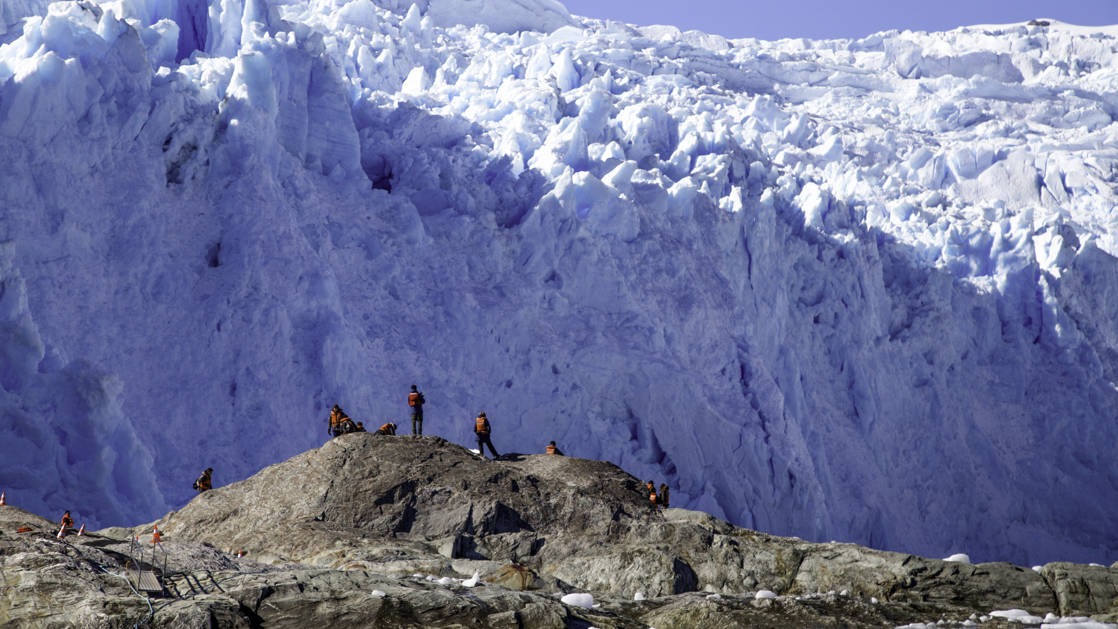Several people standing on rocks in front of a massive blue and white glacier in Patagonia