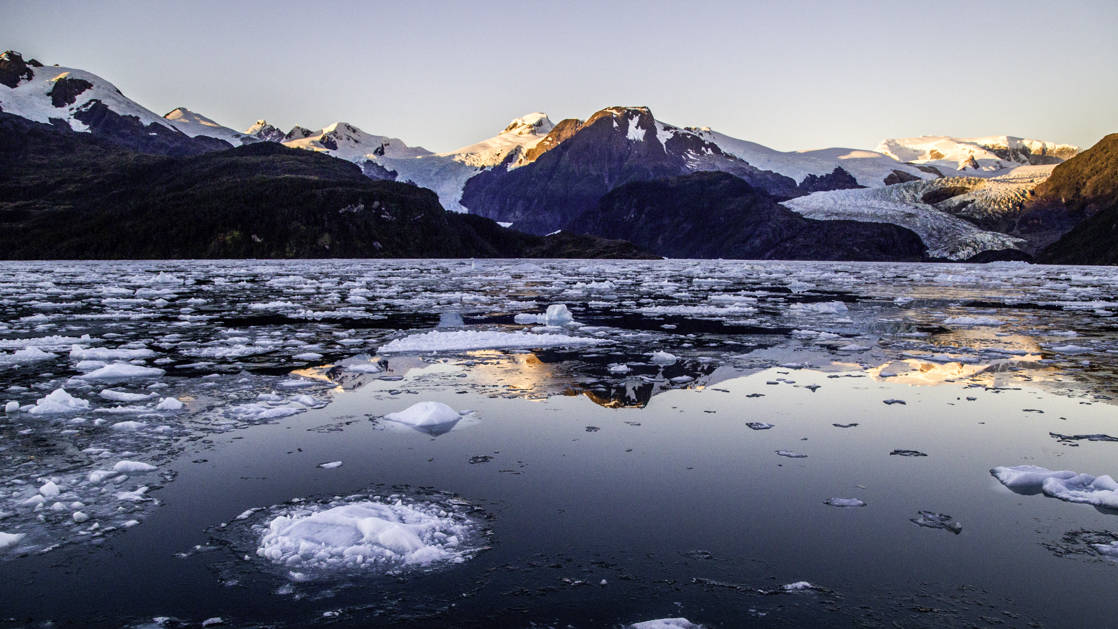 Ice on the calm and reflective water in front of a glacier in Tierra Del Fuego, Patagonia, during sunset